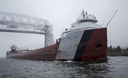 通过在空中升降吊桥下的货轮船 库存图片