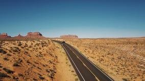 通过在空的沙漠高速公路路的寄生虫照相机的蓝色提取汽车在有使的平的山地平线惊奇亚利桑那 影视素材