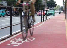 通过在自行车车道的自行车标志的骑自行车者 背景迷离弄脏了抓住飞碟跳的行动 免版税库存照片