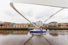 通过在被掀动的千年桥梁下的小船在新堡,英国 库存照片