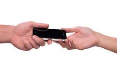 通过巧妙的电话的手 免版税库存图片