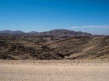 通过巨大岩石山纹理全景风景视图背景层数冒险在土路旅行的旅途场面 免版税库存照片