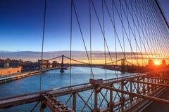 通过布鲁克林大桥降低曼哈顿在日落,纽约 免版税库存图片