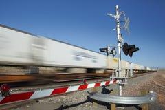 通过平交路口行动迷离的火车 免版税库存照片