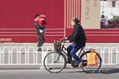 通过广告牌,北京,中国的自行车的年长妇女 免版税库存图片