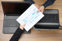 通过报告的会议的女实业家对伙伴,顶视图wi 库存图片