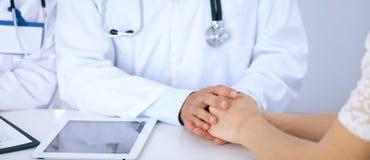 通过接触她的手篡改再保证他的女性患者,当谈话时 支持和信任的标志在医学 免版税库存图片