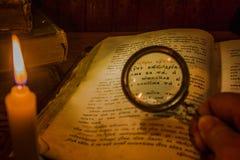 通过放大镜审查古老祈祷书的文本 图库摄影