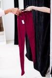 通过新的妇女s牛仔裤的女性手对商城的一个贴合摊 免版税图库摄影