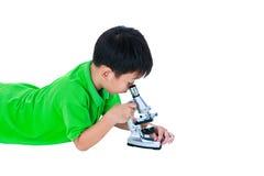 通过显微镜生物准备被观察的亚裔孩子 免版税库存图片