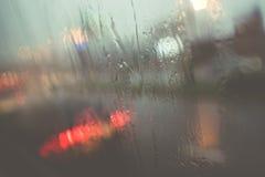 通过有有些雨珠的湿挡风玻璃被看见的汽车被弄脏的光  库存照片