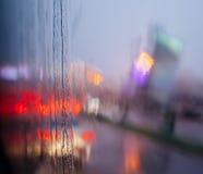 通过有有些雨珠的湿挡风玻璃被看见的汽车被弄脏的光  免版税图库摄影