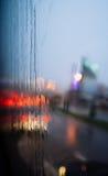 通过有有些雨珠的湿挡风玻璃被看见的汽车被弄脏的光  图库摄影