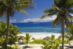 通过棕榈树被看见的帆船, Mamanuca小组海岛,斐济 图库摄影