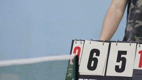 通过比赛板,打乒乓球 坐在委员会后的男性翻转数字比分  股票录像