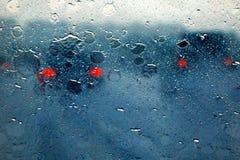 通过水被看见的模糊的汽车剪影在汽车挡风玻璃滴下 免版税库存图片