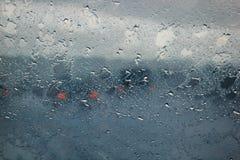 通过水被看见的模糊的汽车剪影在汽车挡风玻璃滴下 免版税图库摄影