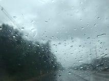 通过汽车的前面挡风玻璃弄脏风雨如磐的灰色天空和雨射击,当驾驶时 免版税库存照片