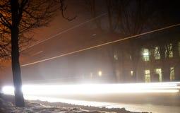 通过汽车轻的轨道在晚上 在夜城市的街道上的雾 免版税库存照片