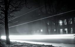 通过汽车轻的轨道在晚上 在夜城市的街道上的雾 库存照片