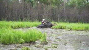 通过沼泽、水、泥和泥驾驶ATV 慢的行动 影视素材