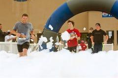 通过泡沫跑的公赛跑者在种族终点线  免版税库存图片