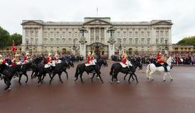 通过白金汉宫的女王的皇家骑马卫兵乘驾 免版税库存照片