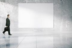 通过空白的广告牌的商人 免版税库存照片