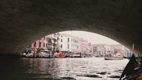 通过紧密在威尼斯大石桥桥梁下的照相机在威尼斯,掀动下来对小船美丽的景色在码头和河沿大厦 影视素材