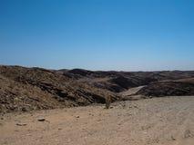 通过纳米比亚沙漠独特的地理巨大岩石山纹理风景背景与分裂的石地面的远航 图库摄影