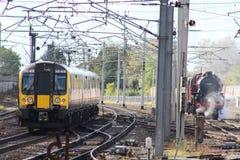 通过老蒸汽火车的现代电鸸火车 免版税库存照片