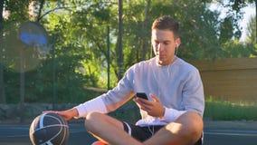 通过耳机和拿着电话,露天的年轻人坐篮球场和滴下的球,听的音乐 股票视频
