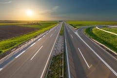 通过被阐明的绿色田园诗领域打开高速公路 库存照片