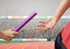 通过警棒的运动员在接力赛期间反对体育场在背景中 免版税库存图片