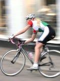 通过赛跑妇女的骑自行车者 库存照片