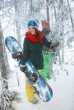 通过进来在冬天森林里的朋友挡雪板 免版税库存图片