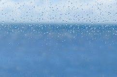 通过透明多雨窗口弄脏大海和天空 库存图片