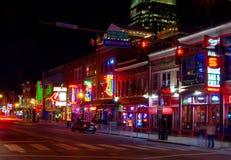 通过酒吧的霓虹灯广告的交通定时曝光在纳稀威娱乐区在晚上 免版税库存照片