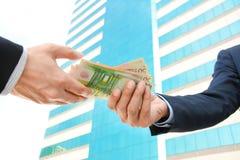通过金钱欧洲货币(EUR)的商人手 库存照片