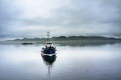 通过驾驶在苏格兰高地的有雾的海的单独小船 免版税库存照片