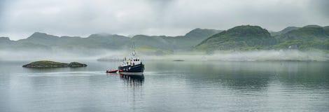 通过驾驶在苏格兰高地的有雾的海的单独小船 图库摄影