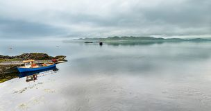 通过驾驶在苏格兰高地的有雾的海的单独小船 库存照片