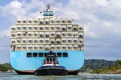 通过巴拿马运河运载的货物被引导和被拖曳的大货船 库存照片