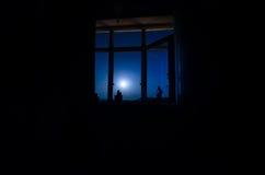 通过从暗室的窗口看的月亮夜场面 免版税库存图片