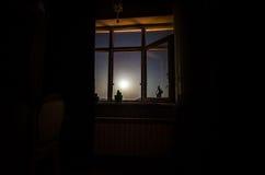 通过从暗室的窗口看的月亮夜场面 库存图片