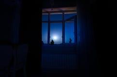 通过从暗室的窗口看的月亮夜场面 图库摄影