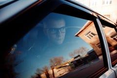 通过玻璃将摩擦汽车的司机 库存图片