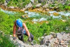 通过ferrata在克罗地亚,Cikola峡谷 攀登一中等困难klettersteig,与Cikola河绿松石颜色的年轻女人 免版税图库摄影