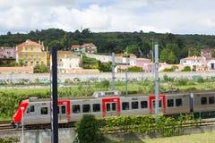 通过S的里斯本市郊火车 多明戈斯de本菲卡队历史的地区,里斯本,葡萄牙 免版税库存照片