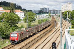 通过S的里斯本市郊火车 多明戈斯de本菲卡队历史的地区,里斯本,葡萄牙 库存图片